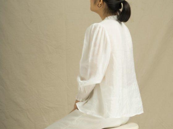 mujer vestida de blanco sentada de espaldas